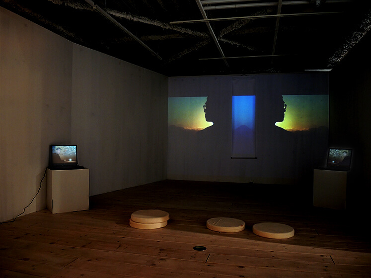 installation view with projection on the wall and 2 computers