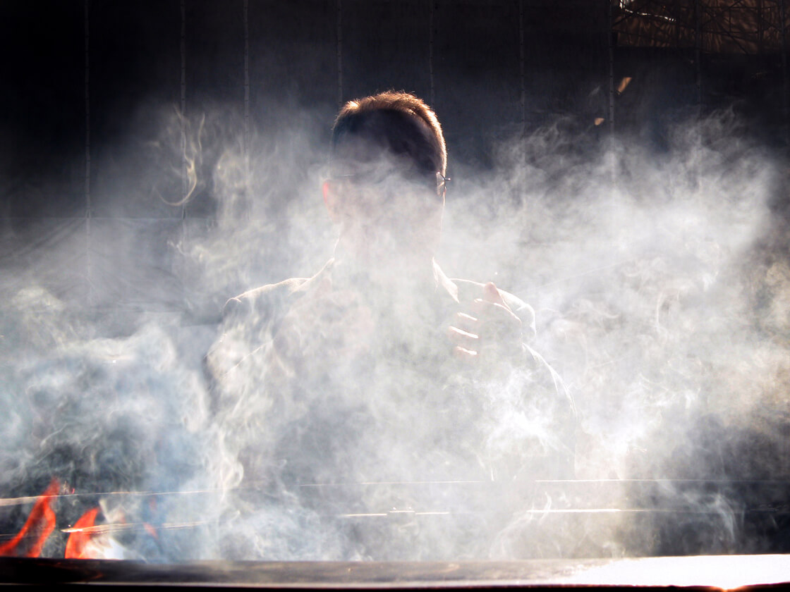 a salaryman behind incense smoke at Sensoji temple