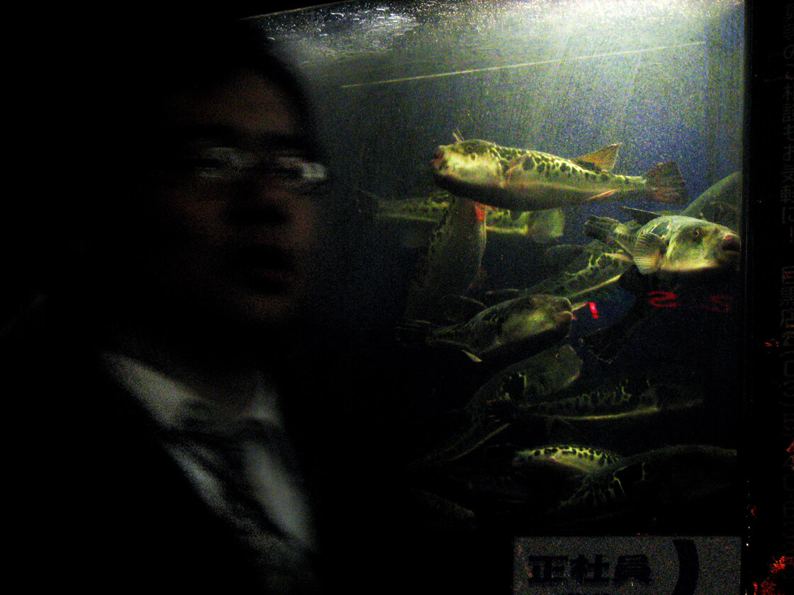 a salaryman in front of a Fugu (pufferfish) restaurant in Meguro