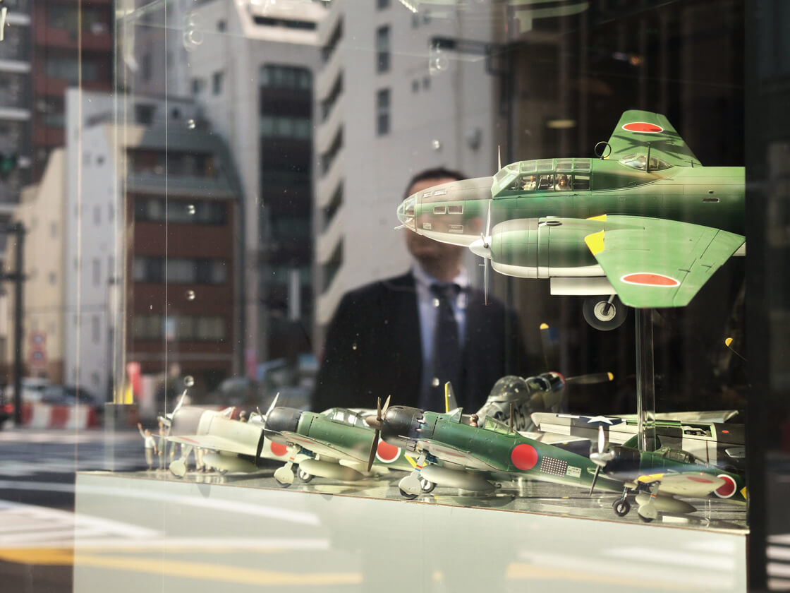 the reflection of a salaryman in a shop selling WW2 plane scale models in Shimbashi