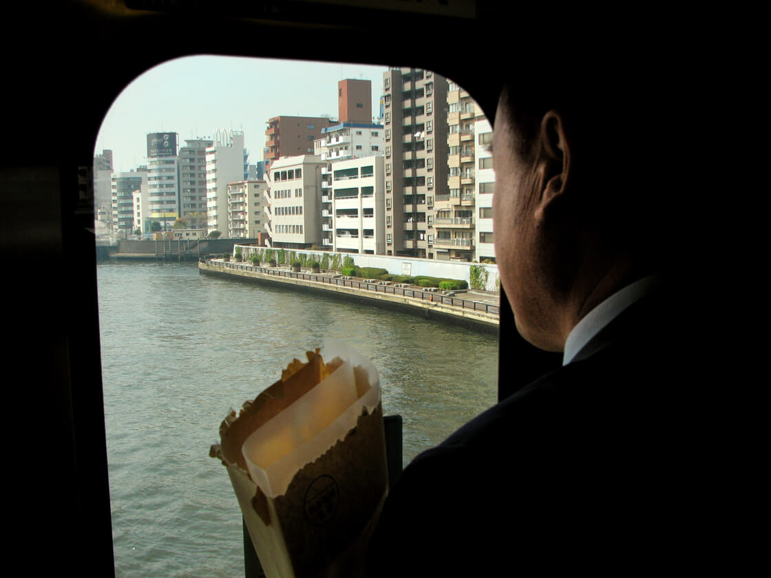a salaryman looking a the Sumida river from the Sobu line train