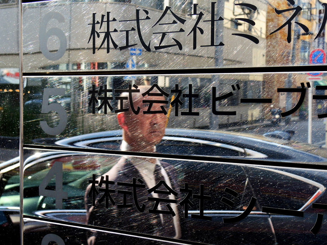 the reflection of a salaryman in a building in Kanda